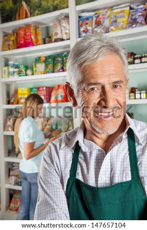 Portrait of happy senior male owner with female customer shopping in background - stock photo