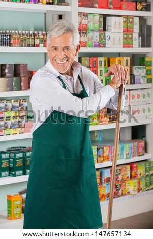 Portrait of happy senior male owner with stick standing against shelves in supermarket - stock photo