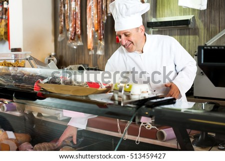 Portrait of happy senior male seller posing with wursts in butchery