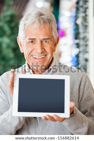 Portrait of happy senior man displaying digital tablet at Christmas store - stock photo