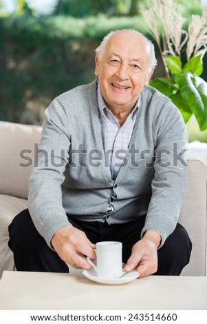 Portrait of happy senior man having coffee on couch at nursing home porch - stock photo