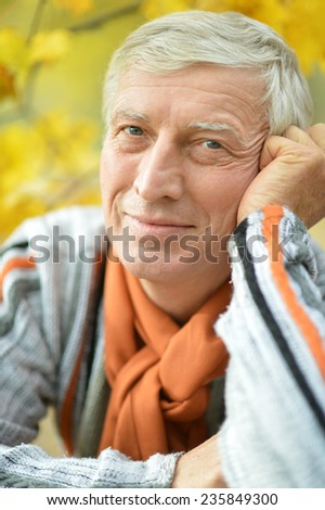 Portrait of happy senior man in the park in autumn