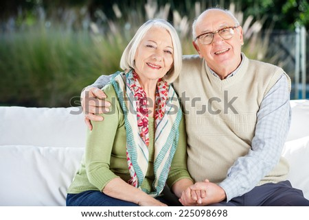Portrait of happy senior man sitting with arm around woman on couch at nursing home porch - stock photo