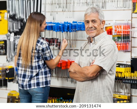 Portrait of happy senior man standing arms crossed with daughter in background at hardware store - stock photo