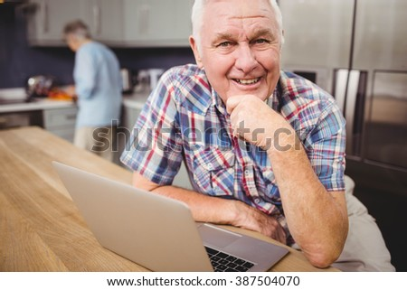 Portrait of happy senior man using laptop and woman working in kitchen at home - stock photo