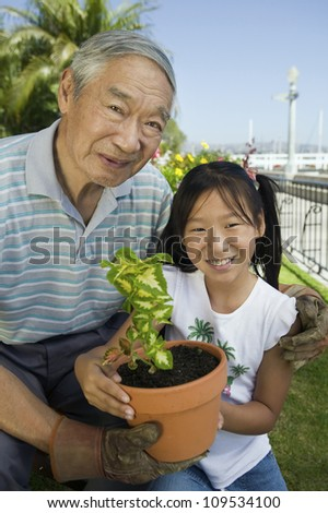 Portrait of happy senior man with granddaughter gardening together - stock photo
