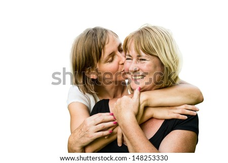 Portrait of happy senior mother kissed by her adult daughter - isolated on white - stock photo
