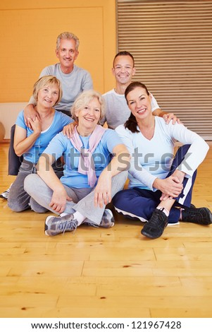 Portrait of happy senior people group sitting in a gym - stock photo