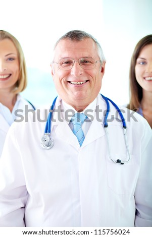 Portrait of happy senior therapeutist looking at camera with his assistants behind - stock photo