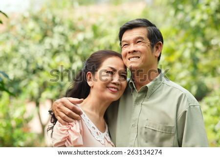 Portrait of happy senior Vietnamese couple outdoors - stock photo