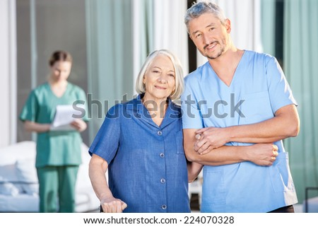 Portrait of happy senior woman and male caretaker standing at nursing home yard - stock photo