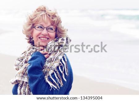 Portrait of happy senior woman at sea - stock photo