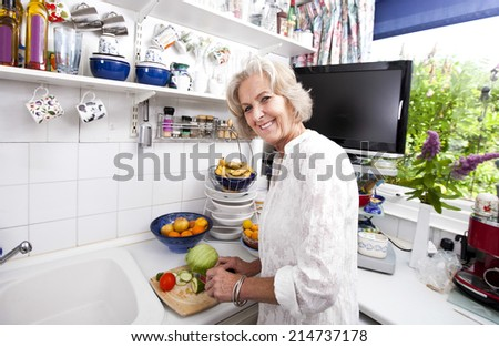 Portrait of happy senior woman chopping fresh vegetables at kitchen counter - stock photo