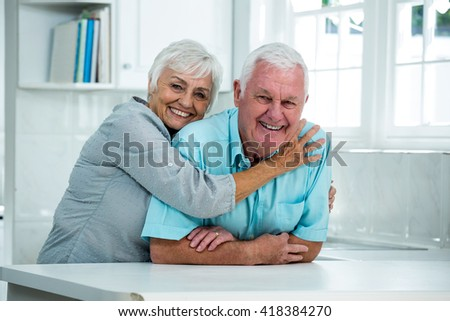 Portrait of happy senior woman embracing man leaning at table in house - stock photo