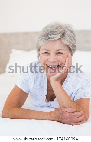Portrait of happy senior woman lying in bed at home - stock photo