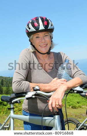 Portrait of happy senior woman on mountain bike
