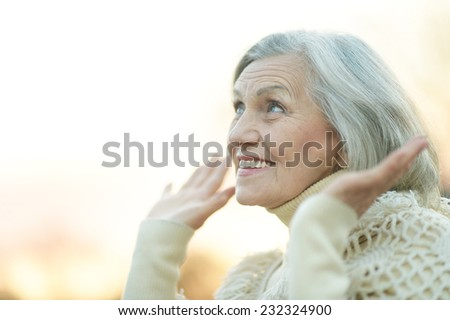 Portrait of happy senior woman outdoors against the sky