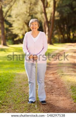portrait of happy senior woman outdoors in park - stock photo