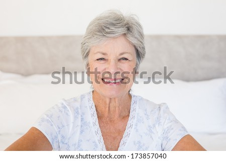 Portrait of happy senior woman sitting on bed at home