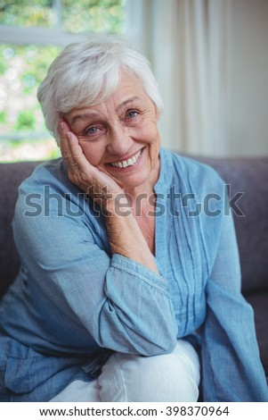 Portrait of happy senior woman sitting on sofa at home