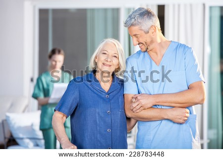 Portrait of happy senior woman standing with male caretaker at nursing home yard - stock photo