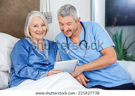 Portrait of happy senior woman using tablet PC with caretaker in bedroom at nursing home - stock photo