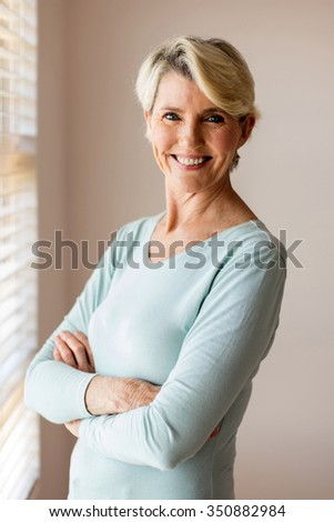 portrait of happy senior woman with arms folded at home