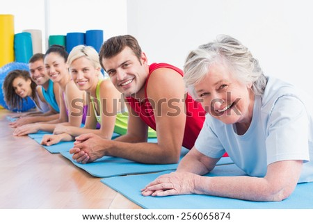 Portrait of happy senior woman with friends lying on exercise mats at gym - stock photo
