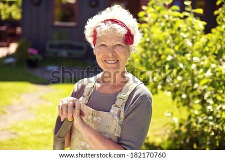 Portrait of happy senior woman with gardening tools standing in backyard garden - stock photo