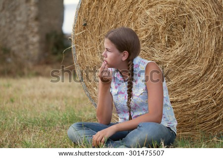 Portrait of happy serious teen sitting on haystack on background of old aqueduct (ruins), outdoor