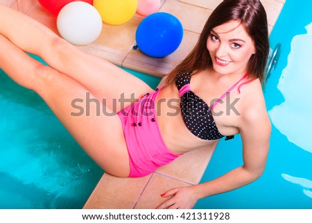 Portrait of happy sexy seductive woman at swimming pool edge poolside. Pretty alluring sensual young girl in bikini relaxing. - stock photo