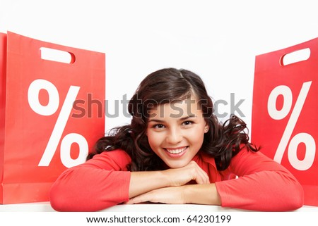 Portrait of happy shopper lying between red paper bags and looking at camera - stock photo