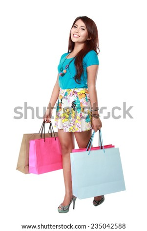 portrait of happy shopping girl holding bags. over white background