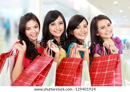 Portrait of happy shopping woman carrying many  shopping bags at the mall - stock photo