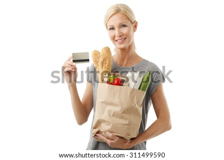 Portrait of happy shopping woman paying by card at the supermarket. Isolated on white background. - stock photo