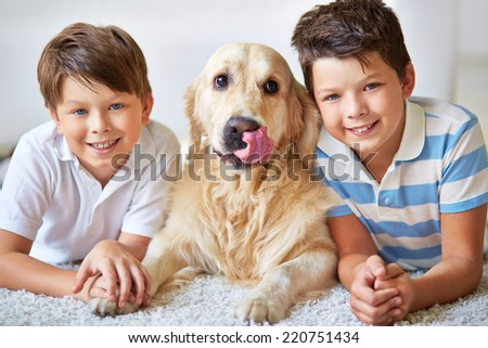 Portrait of happy siblings and their pet lying on the floor - stock photo
