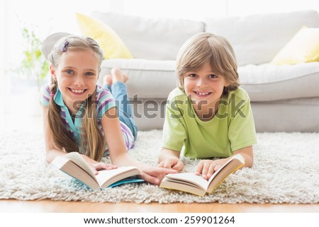Portrait of happy siblings holding books while lying on rug in living room - stock photo