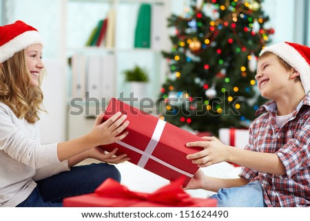 Portrait of happy siblings holding giftbox and looking at one another on Christmas evening - stock photo