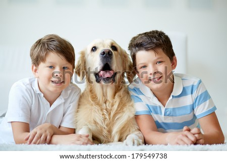 Portrait of happy siblings with their pet having rest at home - stock photo