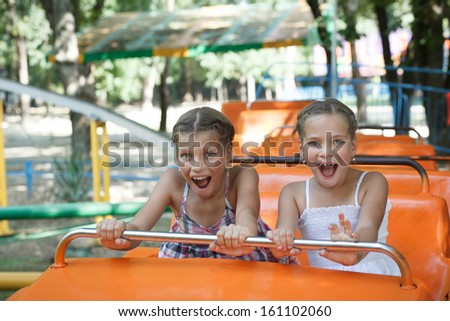 Portrait of happy sisters enjoying themselves on carousel - stock photo