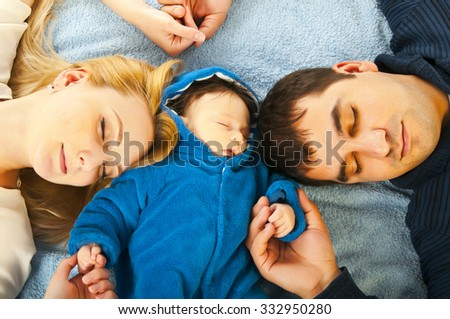 Portrait of happy sleeping young family with little kid holding hands - stock photo