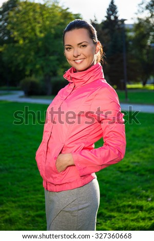 portrait of happy slim woman in sportswear walking in evening autumn park