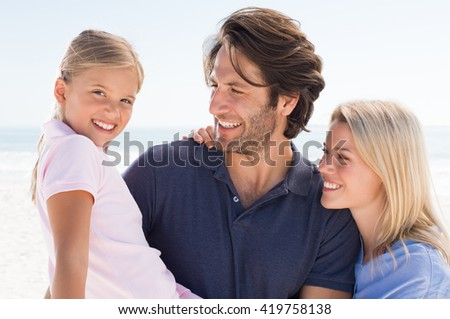 Portrait of happy small family at beach. Little girl in father arm looking at camera. Parent enjoying vacation with child. - stock photo