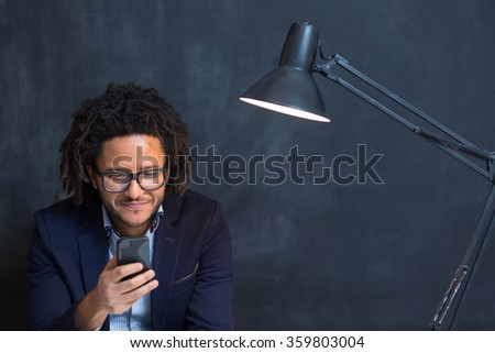 Portrait of happy smart black businessman sitting at desk in office, mulit race hipster in office on chalkboard background, afro using phone, typing message - stock photo