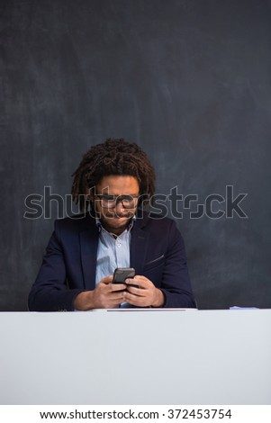 Portrait of happy smart black businessman sitting at desk in office, mulit race hipster in office on chalkboard background - stock photo