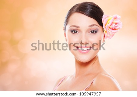 portrait of happy smiley model with rose in hair