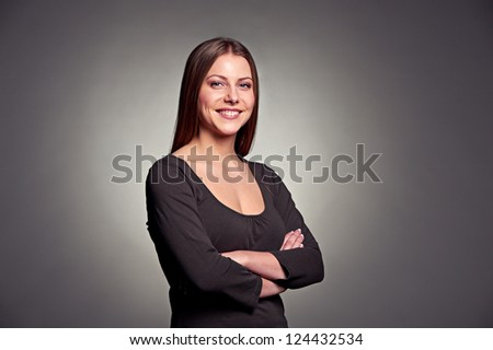 portrait of happy smiley woman with crossed hands over dark background - stock photo