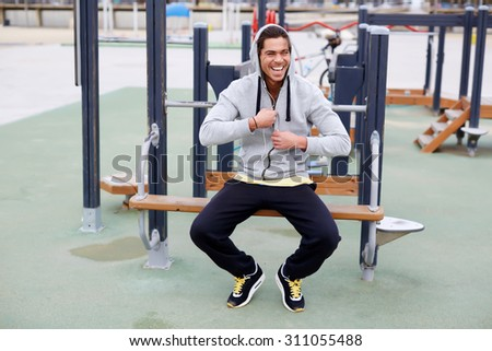 Portrait of happy smiling athlete in sportswear resting after an active workout while sitting on training apparatus outdoors at cloudy day,happy male runner taking a break after a morning workout - stock photo
