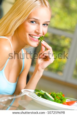 Portrait of happy smiling beautiful blond woman eating salad - stock photo
