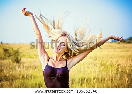Portrait of happy smiling beautiful girl amongst the field - stock photo
